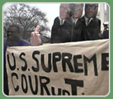 Man holding sign that reads, U.S. Supreme COURupTion